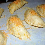 Fold, seal and top with grated cheese.